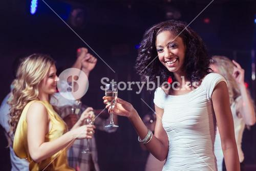 Portrait of woman holding champagne flute while dancing