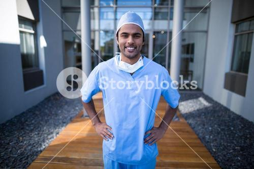 Portrait of male surgeon standing with hands on hip