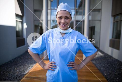 Portrait of female surgeon standing with hands on hip