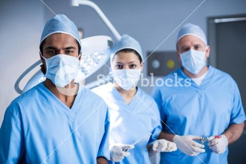 Portrait of surgeons holding surgical tool in operation room