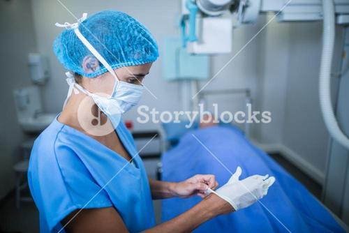 Nurse wearing surgical gloves in x-ray room