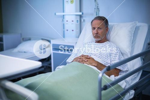 Sick patient sitting on bed