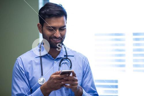 Doctor text messaging on mobile phone