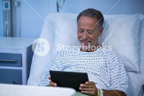 Sick patient sitting on bed and using digital tablet