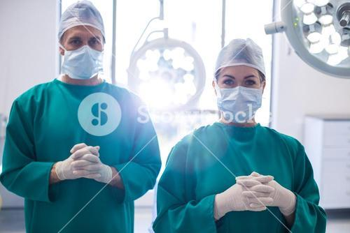 Portrait of surgeons standing with hands clasped in operation room
