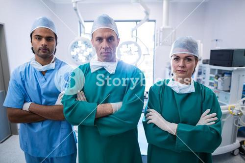 Portrait of surgeons standing with arms crossed in operation room