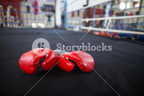 Pair of red gloves in boxing ring