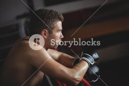 Boxer leaning on boxing ring