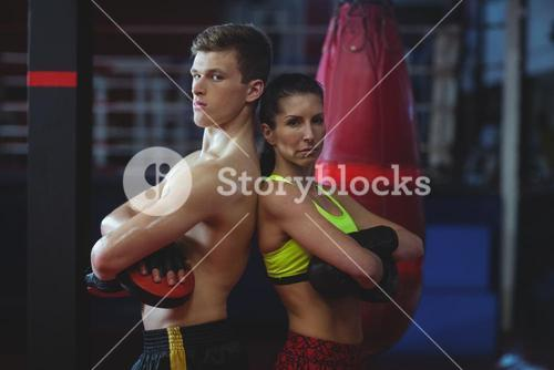 Female and male boxer standing back to back