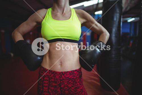 Female boxer standing with hands on hip