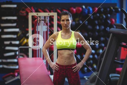 Sportswoman standing with hands on hip