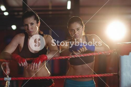 Two female boxers standing in boxing ring
