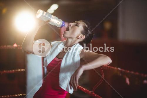 Female boxer drinking water in boxing ring