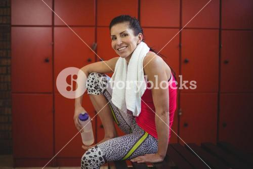 Woman sitting in gym locker room after workout