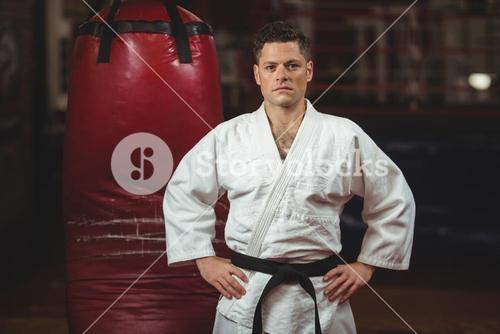 Karate player with hands on hips standing in fitness studio