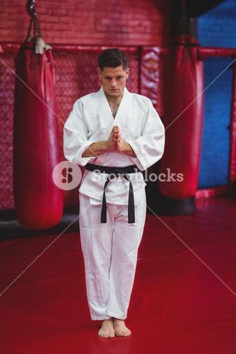 Karate player standing in prayer pose