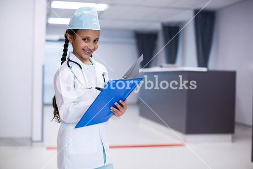 Girl writing on clipboard while pretending herself as a doctor