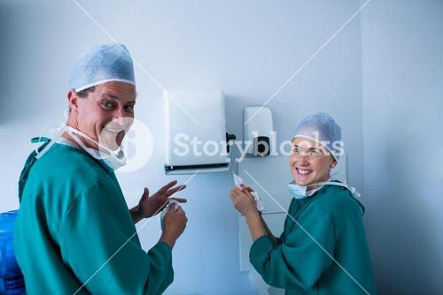 Portrait of happy surgeons cleaning their hands after operation