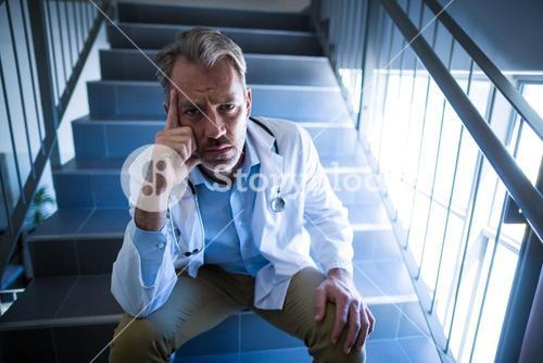 Portrait of sad doctor sitting on staircase
