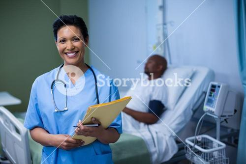 Portrait of female nurse standing with file in ward
