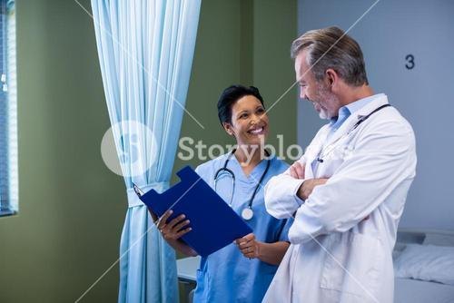 Doctor and nurse having discussion on file in ward