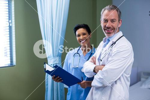 Portrait of doctor and nurse standing in ward