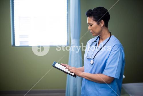 Female nurse using digital tablet in ward