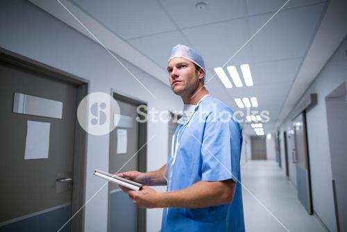 Male nurse using digital tablet in corridor