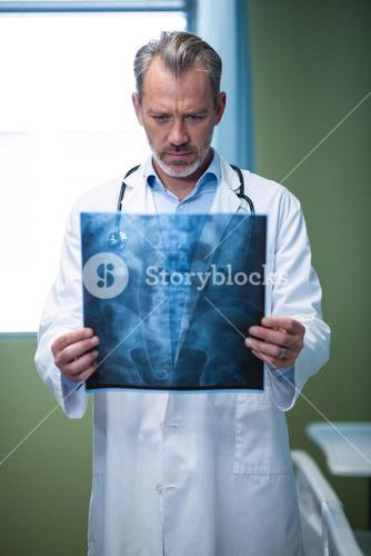 Doctor analyzing patient x-ray in ward