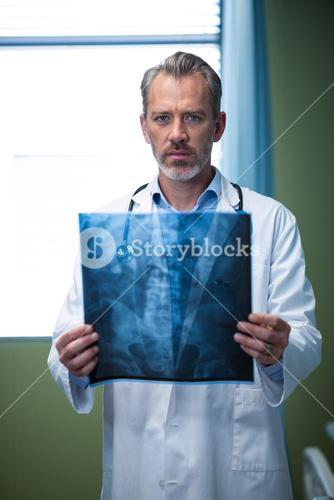 Portrait of doctor analyzing patient x-ray in ward