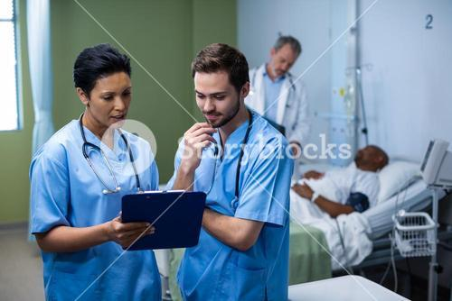 Male and female nurse having discussion over clipboard in ward