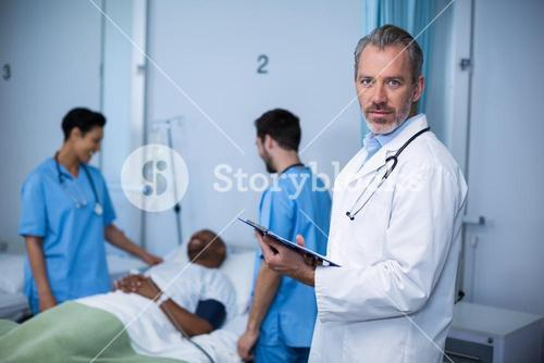 Portrait of doctor writing on clipboard