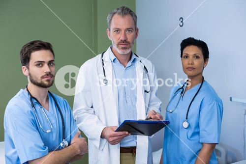 Portrait doctor and nurse discussing over clipboard in ward