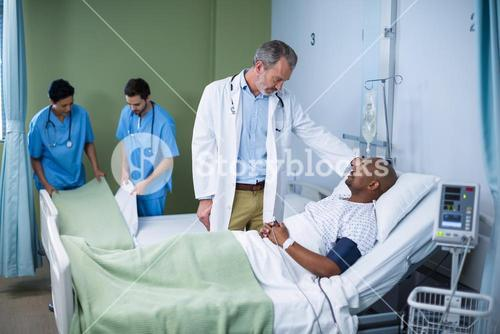 Doctor interacting with patient in ward