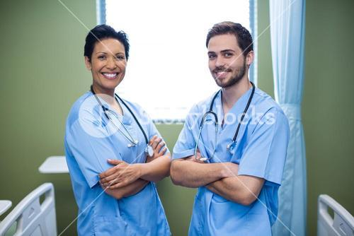 Portrait of male and female nurse standing in ward