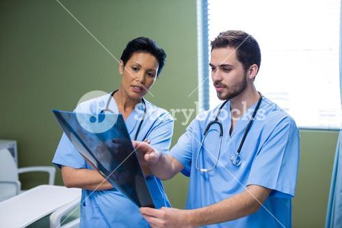 Male and female nurse discussing x-ray in ward