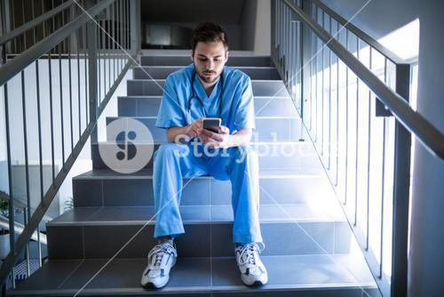 Male nurse sitting on staircase and using mobile phone