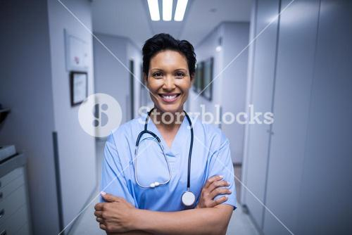Portrait of female nurse standing in corridor