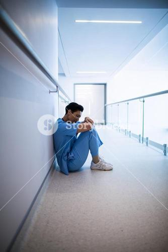 Tensed female nurse sitting in corridor