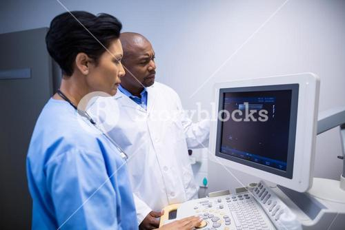 Doctor and nurse using patient monitoring machine in ward