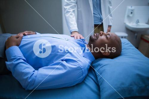 Doctor consoling a patient on bed