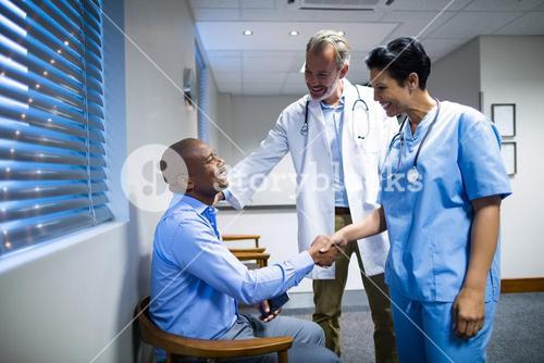 Doctors shaking hands with patient