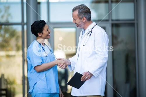 Nurse and doctor shaking hand
