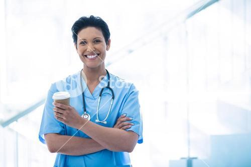 Female nurse standing with disposable cup in corridor