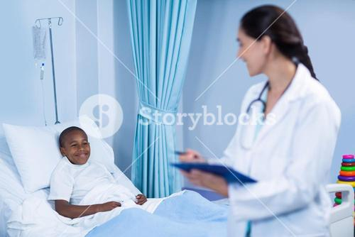 Female doctor checking fever from digital thermometer