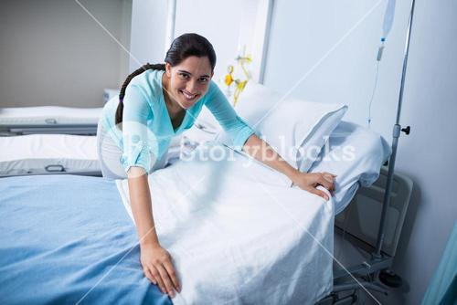 Portrait of doctor preparing bed for patient