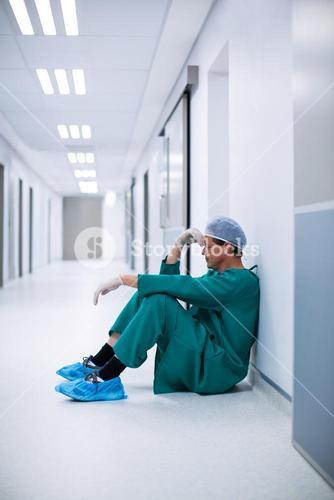 Tensed male surgeon sitting in corridor