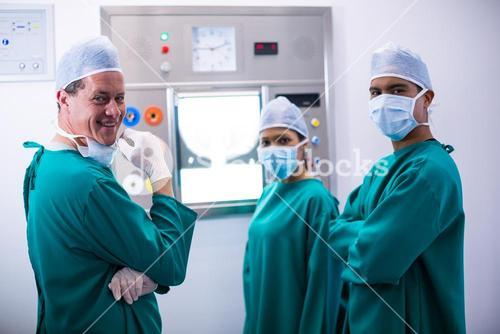 Surgeons discussing a report on surgical monitor in operation room