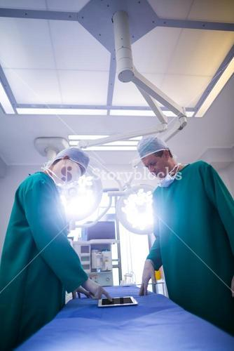 Surgeons discussing over digital tablet in operation room