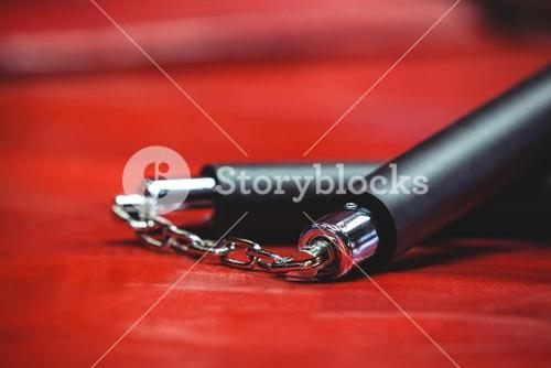 Nunchaku on red background